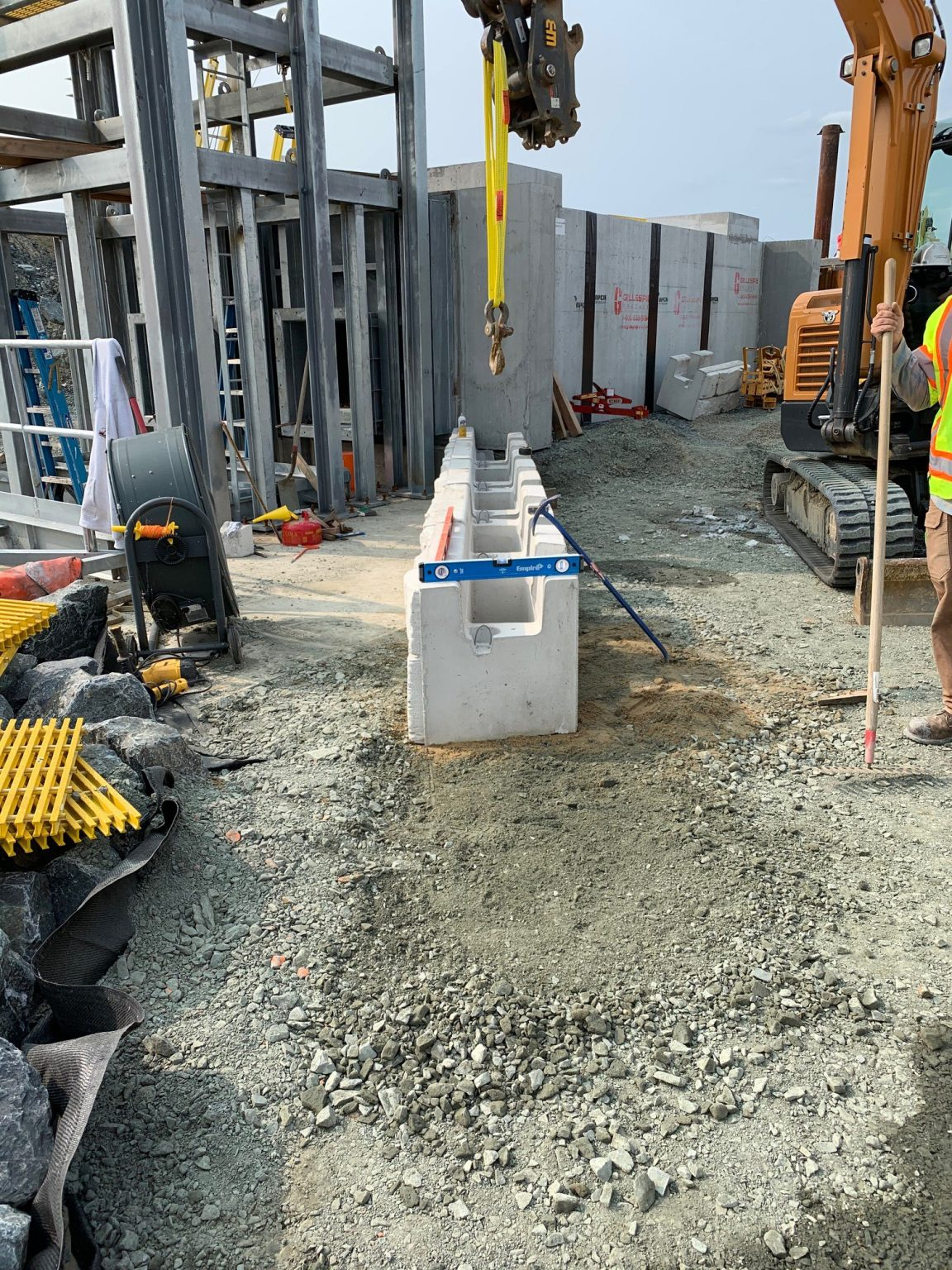 MaxumStone base units being installed on base levelling pad in a commercial application