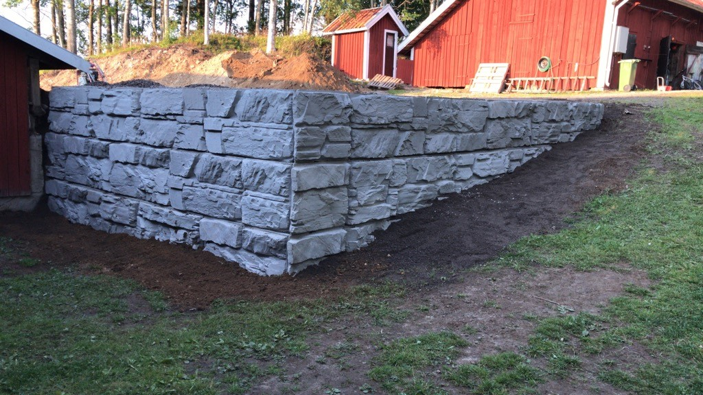 MaxumStone Wall with an outside corner, roughly 6 feet high in a residential backyard in Sweden