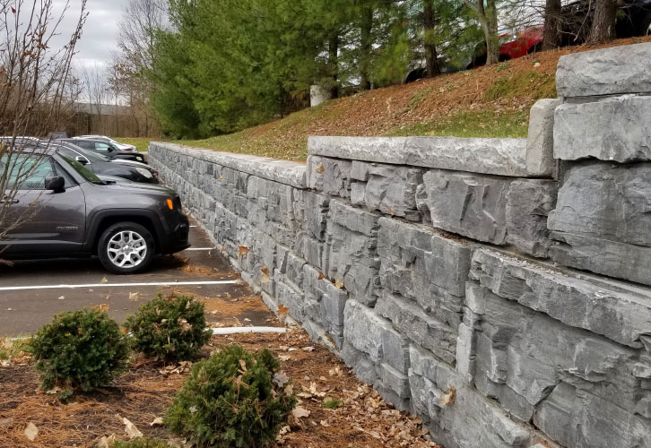 MaxumStone Gravity Retaining Wall Commercial Parking Lot, with a slope on top of the wall