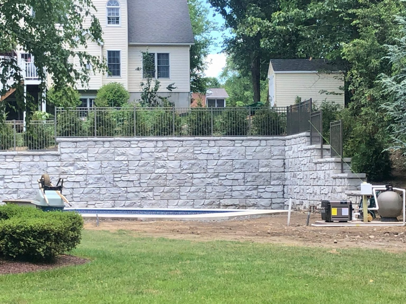 MaxumStone 12 foot retaining wall in a backyard, allowing room for a swimming pool. The wall features an inside corner and top of wall details like caps, fence posts, and step ups.