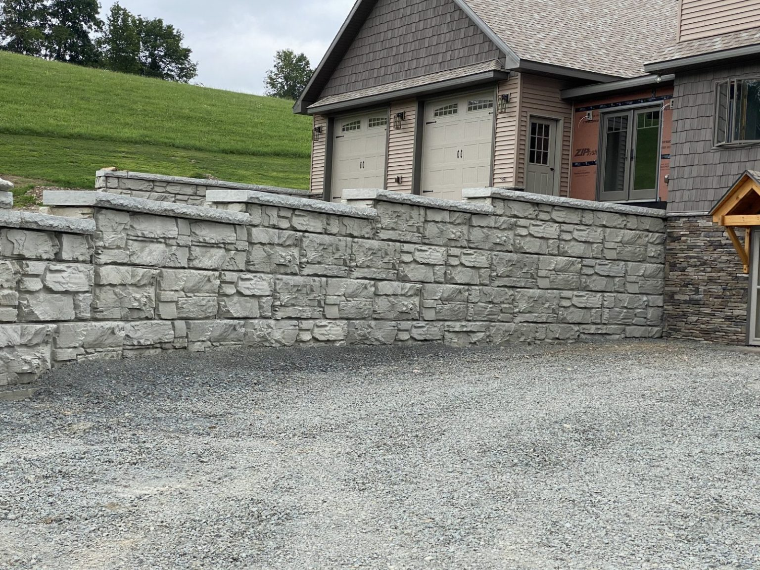 MaxumStone Retaining Wall used to extend a driveway. It features a step-up wall leading up to the home.